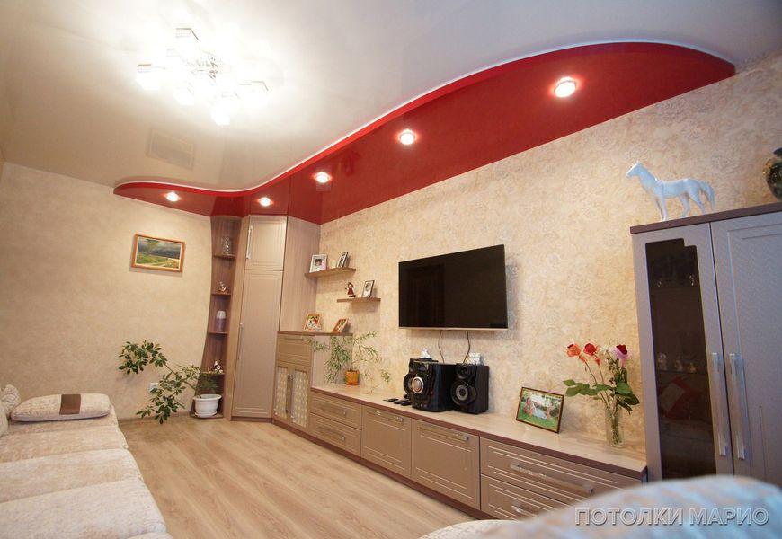 Двухуровневый натяжной потолок в гостиной из белого и красного глянца, внутри которого спрятана многоцветная светодиодная подсветка